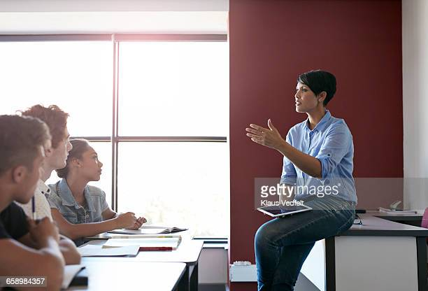 Teacher holding tablet, explaining to class