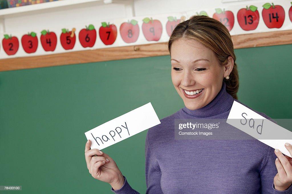 Teacher holding up signs : Stockfoto