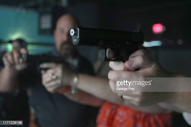 Teacher holds a modified Glock 19 as Utah County Sheriff officers give instructions to teachers before a video simulator is used to teach active...