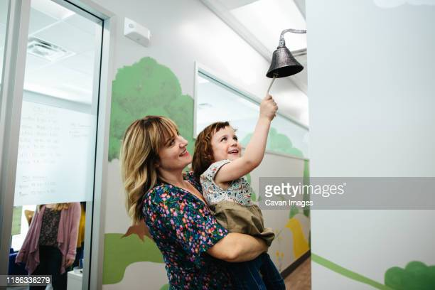 teacher holds little girl up so that she can ring a bell in a school - bell stock pictures, royalty-free photos & images