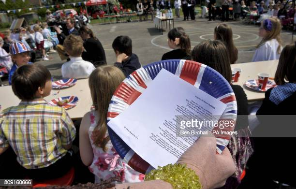 A teacher holds lyrics written by the pupils and staff from the Bucklebury Church of England Primary School for a song they are singing to celebrate...