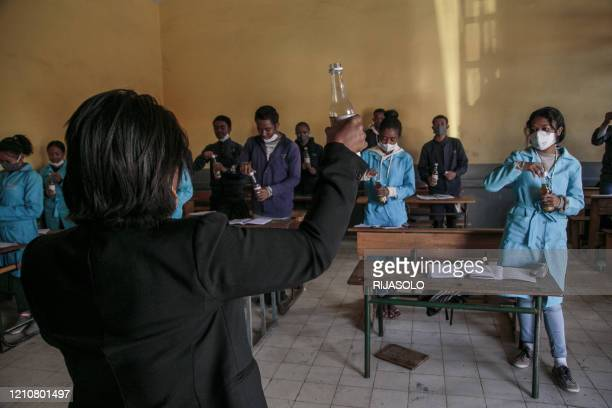 Teacher holds up a bottle of Covid Organics, a herbal tea, touted by Madagascar President Andry Rajoelina as a powerful remedy against the COVID-19...