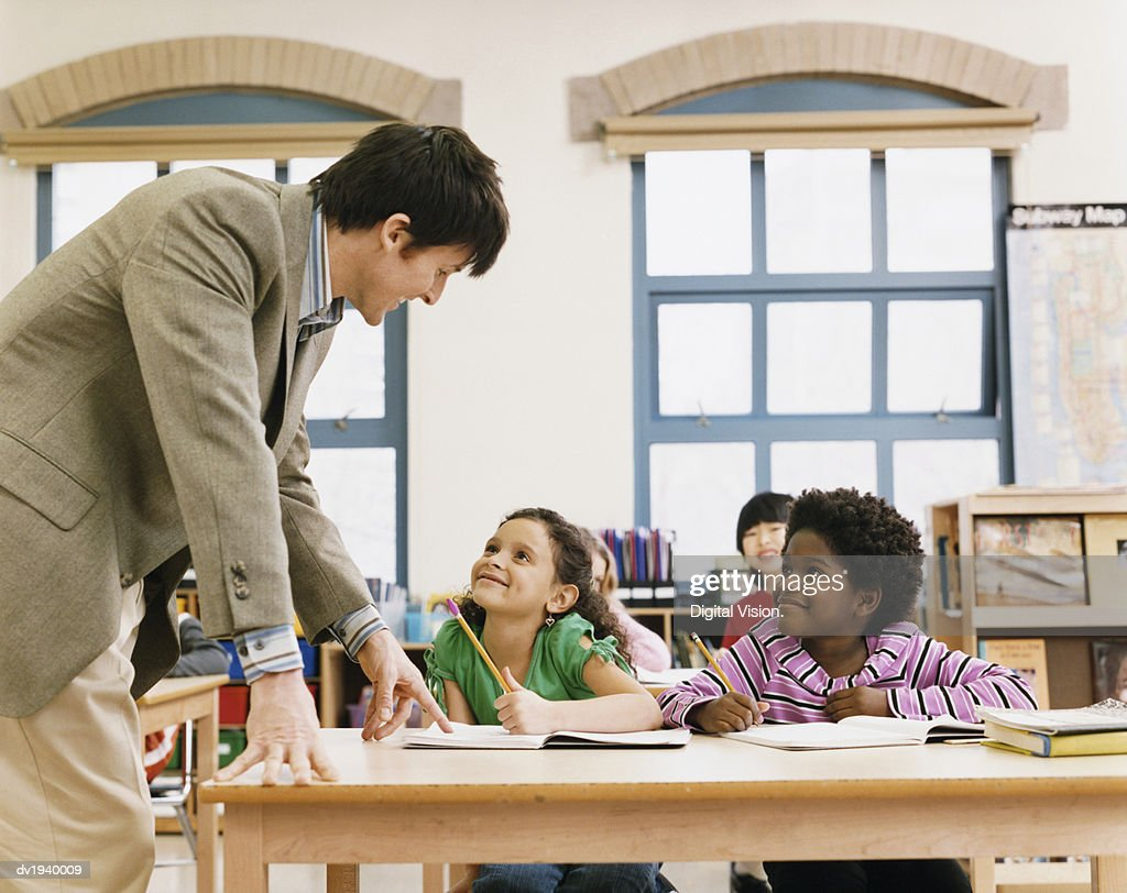 Teacher in a Classroom Helping Primary School Children : Stock Photo