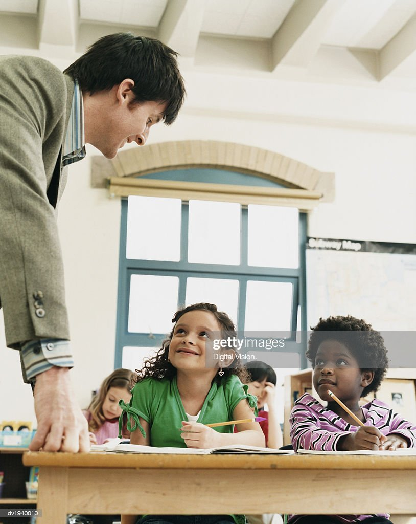 Teacher in a Classroom Helping Primary School Children : Stock Photo
