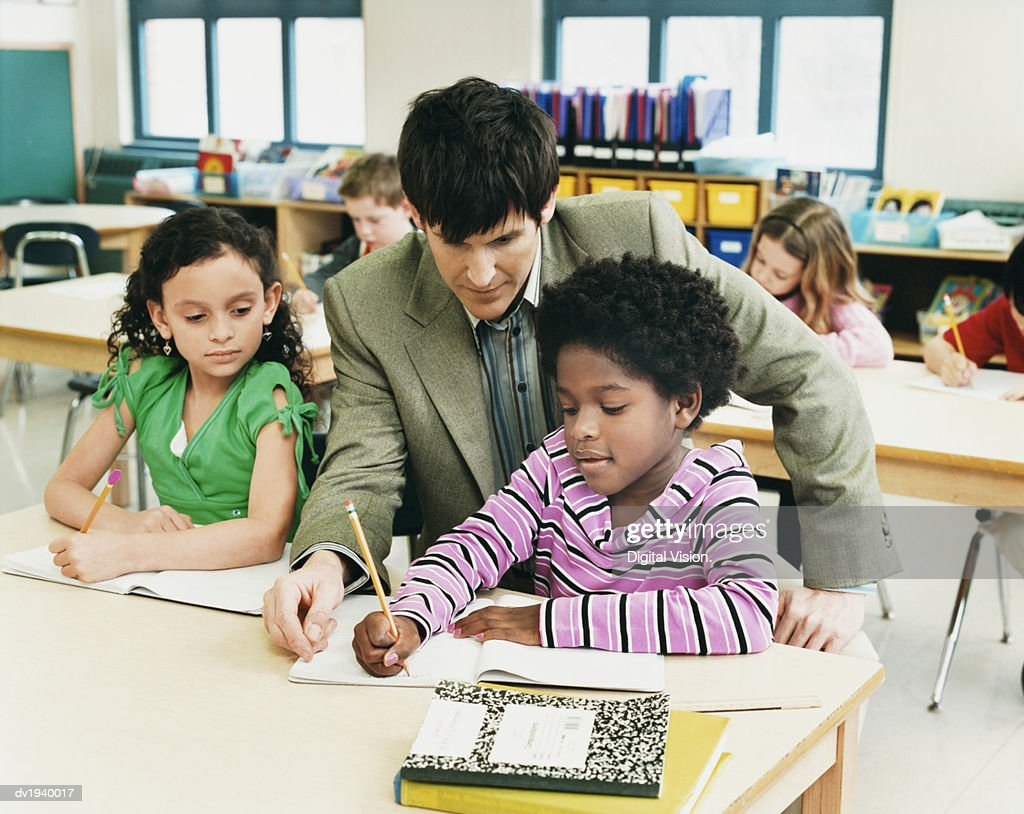 Teacher in a Classroom Helping Primary School Students With Their Work : Stock Photo