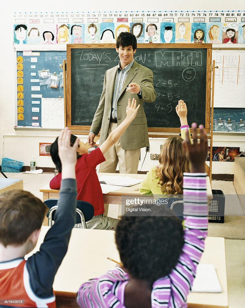 Teacher in a Classroom Pointing at Pupils With Raised Hands : Stock Photo