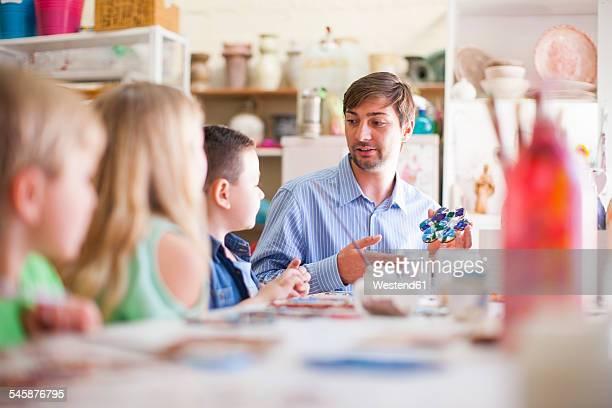 Teacher in arts class talking to pupils