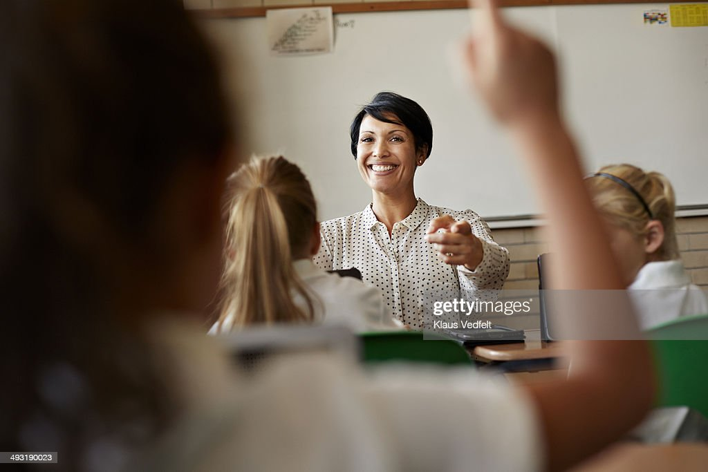 Teacher in class picking student with raised hand : Stock Photo