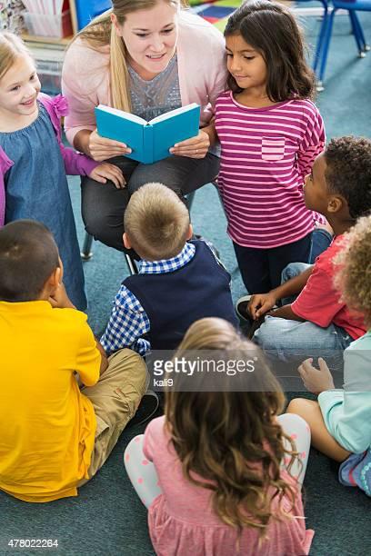 Teacher in class with multiracial group of preschoolers