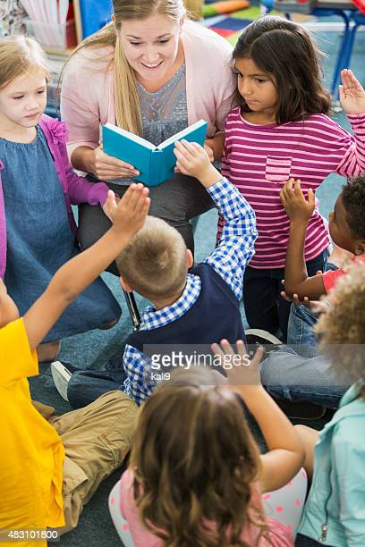 teacher in class with multiracial group of preschoolers - vertical stock pictures, royalty-free photos & images