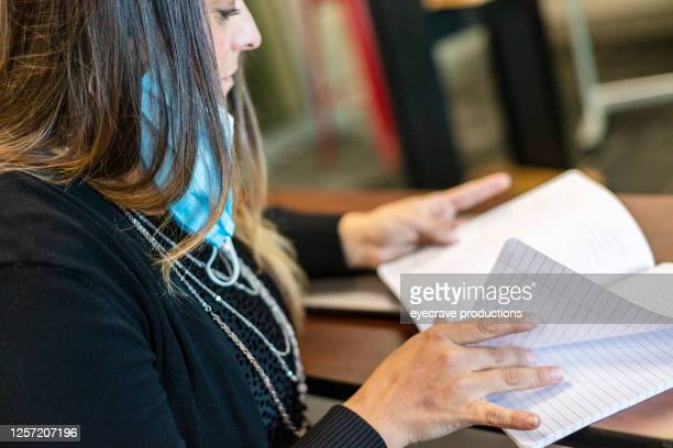 teacher in classroom grading homework with face mask draped over ear - eyecrave  stock pictures, royalty-free photos & images
