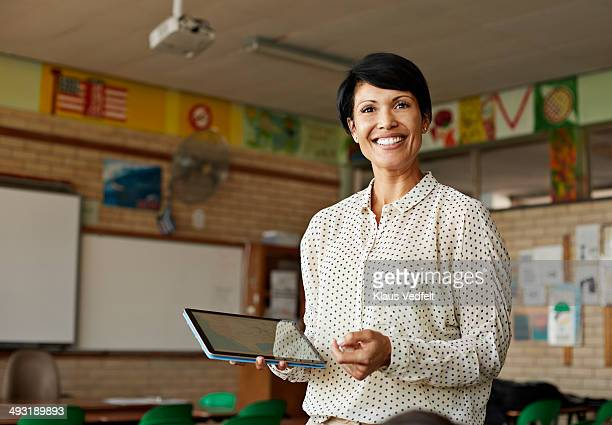 teacher in classroom holding tablet - lehrkraft stock-fotos und bilder