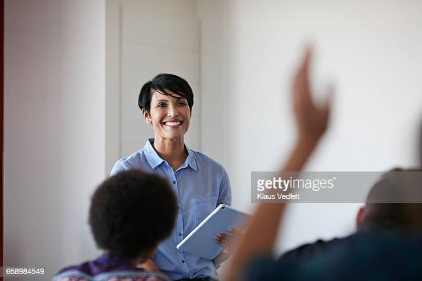 Teacher in front of student, raised hand