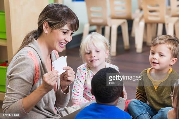 Teacher in preschool classroom with group of children