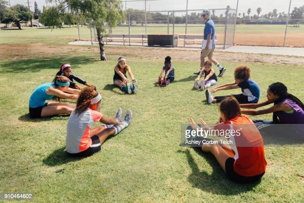 teacher instructing schoolgirl soccer players in warm up on school sports field - pe teacher stock photos and pictures