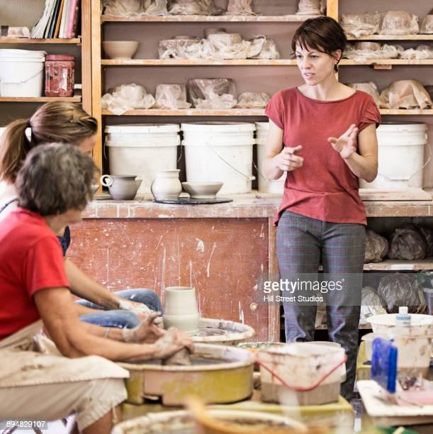 Teacher instructing students in ceramic studio