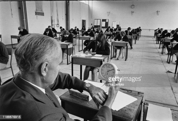Teacher invigilator checks his watch against a time keeping clock as pupils sit at desks writing during a subject examination in the gymnasium of a...