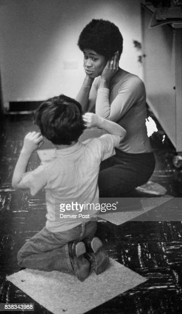 Teacher Jo Keel a developmental dance therapist and student hold hands over ears during class session on different rhythms Credit Denver Post