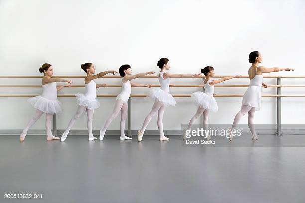 teacher leading pupils (9-13) at bar in ballet class, side view - barre class stock photos and pictures
