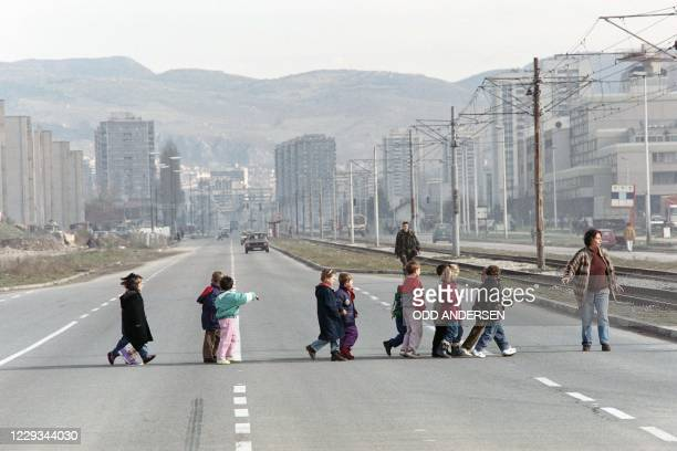 Teacher leads her school class of six and seven-year old children over the infamous Sniper Alley in Sarajevo, on November 16, 1995.