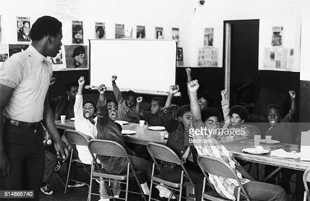A teacher leads his students with the black power salute and slogans at a Black Panther liberation school