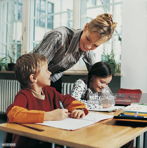 teacher leaning on a desk helping primary school children to write - teacher bending over stock photos and pictures