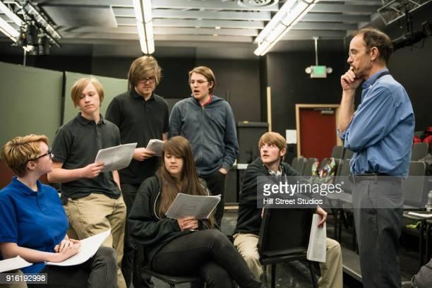 Teacher listening to students reading script