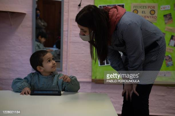 "Teacher listens to a pre-school boy working in his ""Ceibalita tablet"" during a class in a public school in Montevideo, amid the COVID-19 novel..."