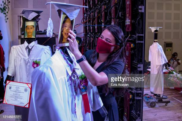 A teacher loads a picture of a graduating student on a tablet attached to a robot during a cyber graduation ceremony at a school on May 22 2020 in...