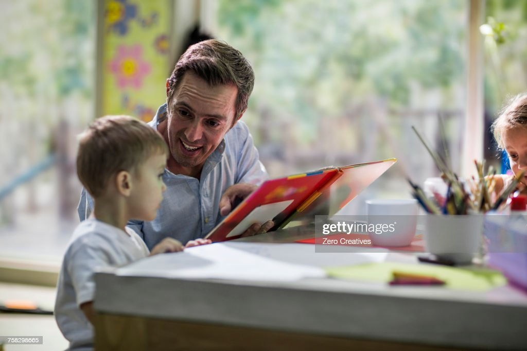 Teacher looking at book with child : ストックフォト
