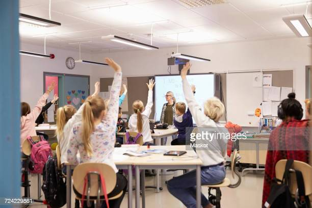 Teacher looking at students with arms raised in classroom