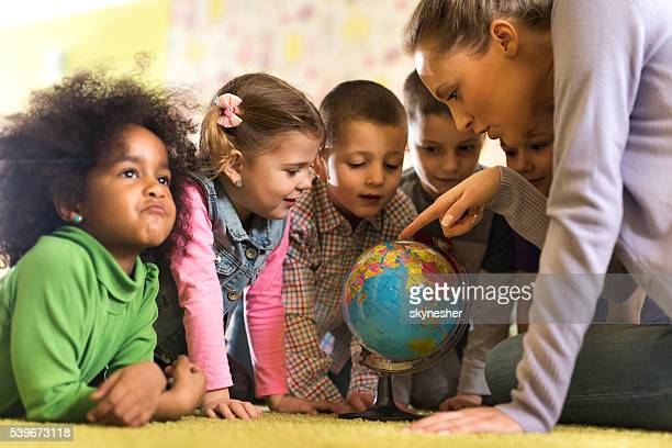 Teacher looking at world globe with group of preschoolers.