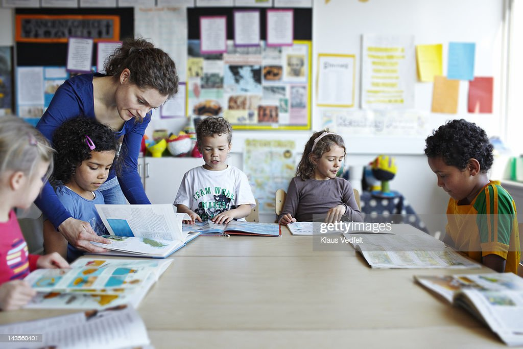 Teacher looking in books with children : Stock Photo