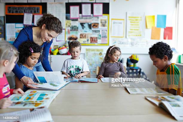 teacher looking in books with children - lehrkraft stock-fotos und bilder