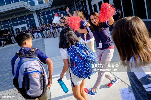 Teacher Margaret Upp and the rest of the teaching staff greet students on the first day of classes at the newly opened Brambleton Middle School on...
