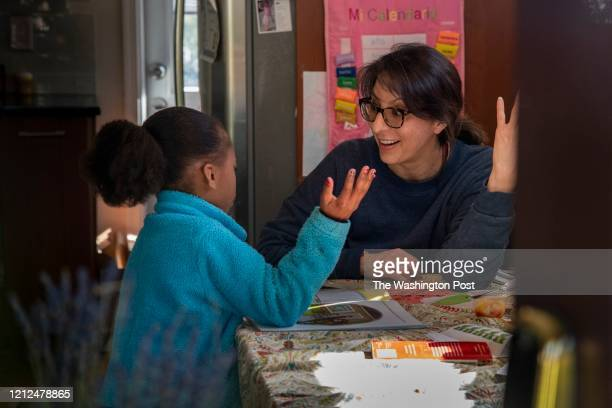Teacher Maria Magallanes, R, homeschools Zola West a child who lives next door, at the Magallanes home in Alexandria, VA, on Friday, April 3, 2020....