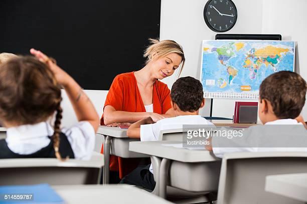 Lehrer markieren/Benoten Hausaufgaben während Studierende Durchführung der Aufgabe