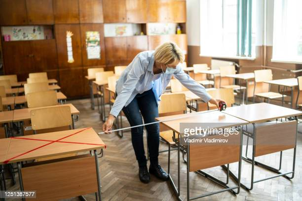 covid-19. teacher marks empty places in the classroom - illness prevention stock pictures, royalty-free photos & images