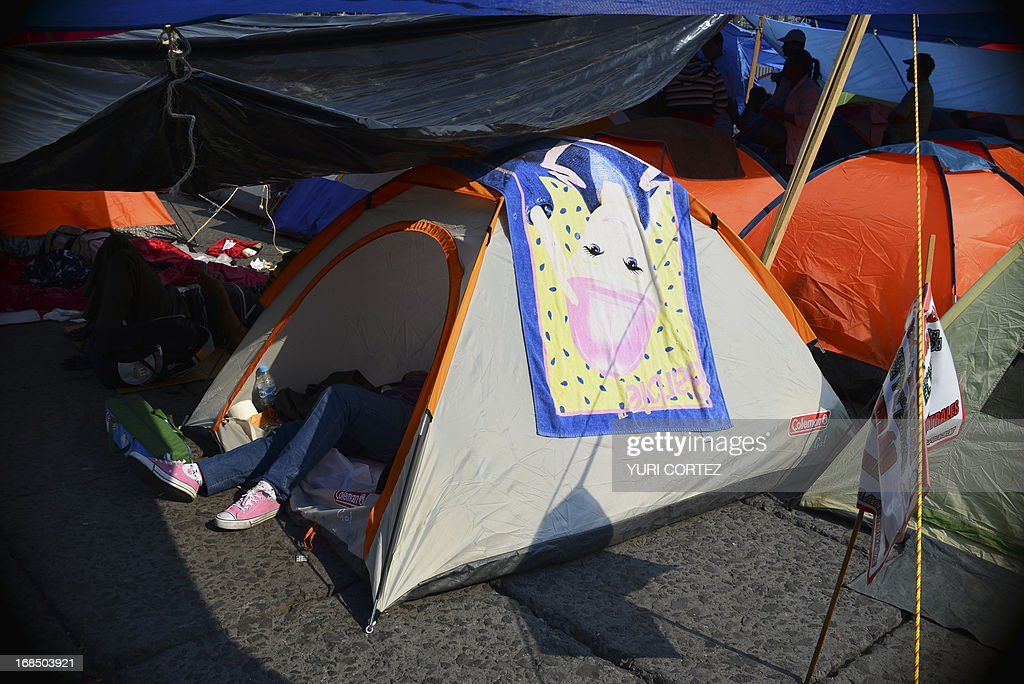 A teacher member of the National Coordinating Committee of Education Workers (CNTE), rests inside a tent set up in front of the National Palace in Mexico City on May 10, 2013. The teachers protest against the educational reform proposed by the Mexican government. AFP PHOTO/ Yuri CORTEZ