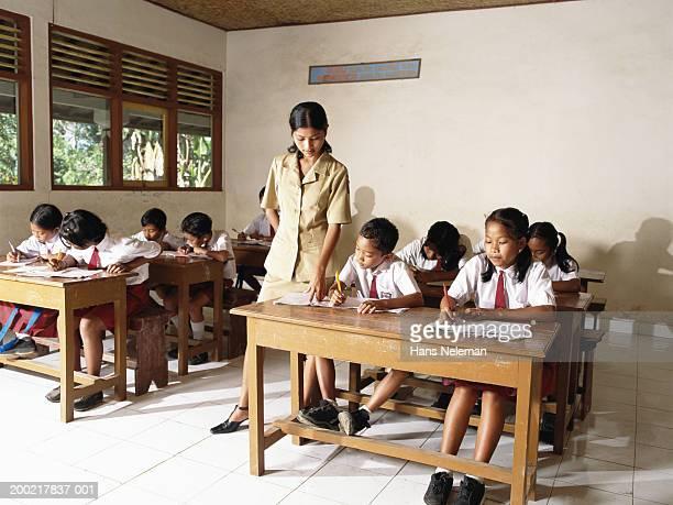 teacher mentoring students (7-10) in classroom - hans neleman ストックフォトと画像