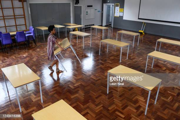 Teacher Muriel Thompson carries a desk into the temporary classroom within the school hall ahead of the return of more students from Reception and...