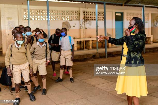 Teacher of Ayany Primary School instruct students in morning of the official re-opening day of public schools on January 4 in Kibera slum, Kenya, as...