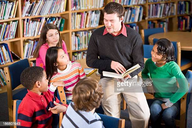 Teacher or librarian reading to group of children