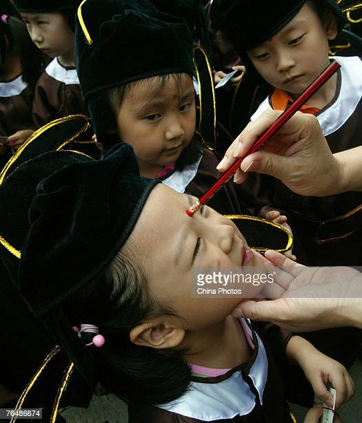 A teacher paints a vermilion dot on the forehead of a student during the 'First Writing' enlightenment ceremony held for grade one students of a...
