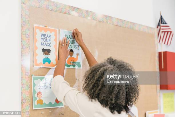 teacher pins covid-19 instructional flyers to bulletin board - bulletin board flyer stock pictures, royalty-free photos & images