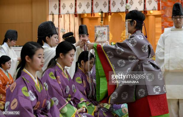 A teacher places an ornament on the head of a female student clad in ancient costume during a traditional adulthood ceremony at Kokugakuin University...