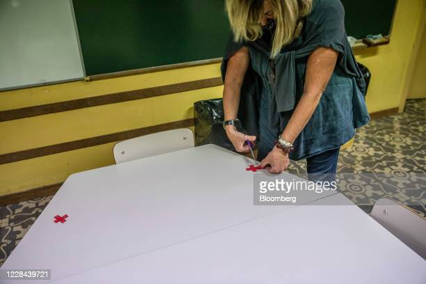 Teacher places markers on desks to assist social distancing inside the classroom of a school for ages 3 to 18 as it prepares to reopen in Barcelona,...