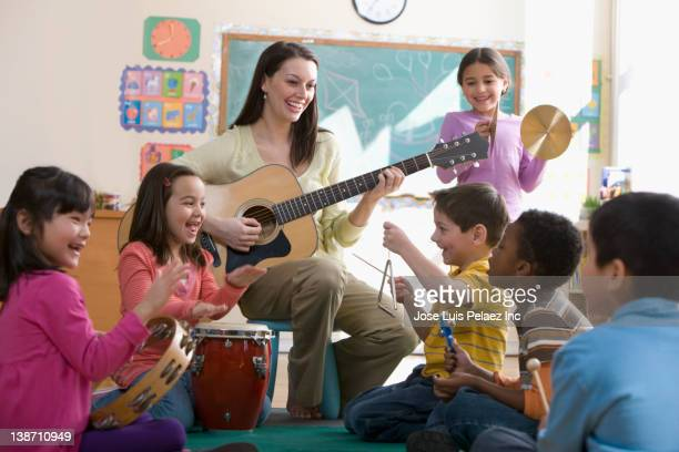 teacher playing guitar for students in classroom - triangle percussion instrument stock photos and pictures
