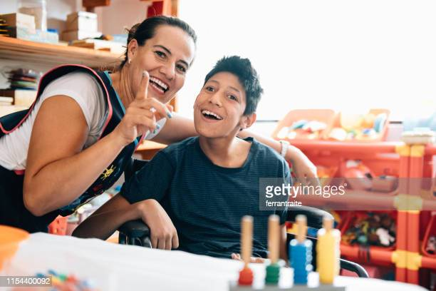 teacher playing with boy with cerebral palsy - family with one child stock pictures, royalty-free photos & images