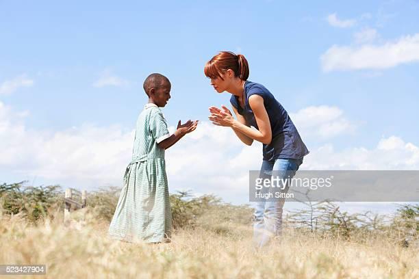 teacher playing with school girl, kenya - hugh sitton photos et images de collection